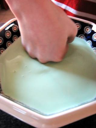 a child making a fist playing with the green oobleck in the bowl