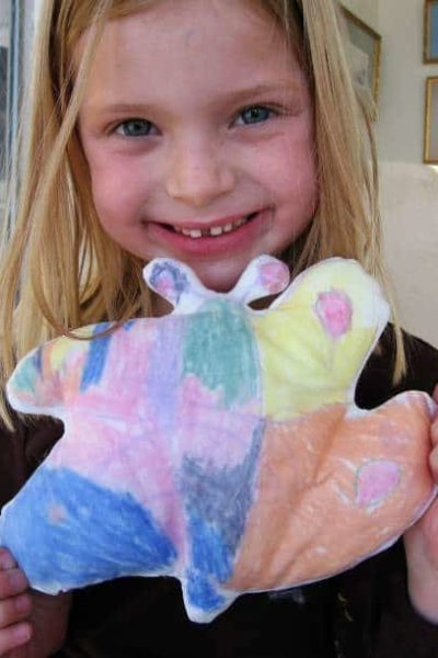 child holding fabric stuffed butterfly made with their drawing
