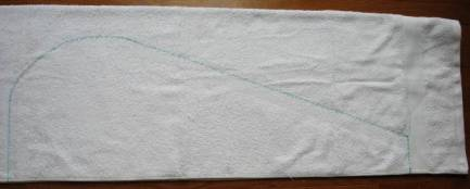 White towel folded in half with pattern traced on it beginning and ending on the folded edge