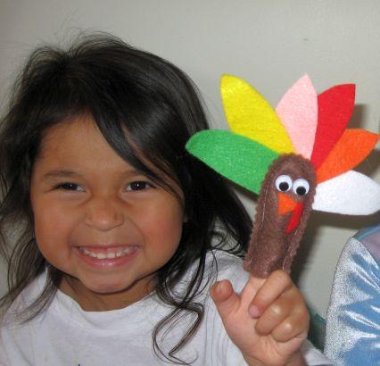 smiling child with turkey finger puppet on finger