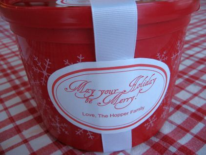 red plastic bucket with white label and white ribbon may you holiday be merry