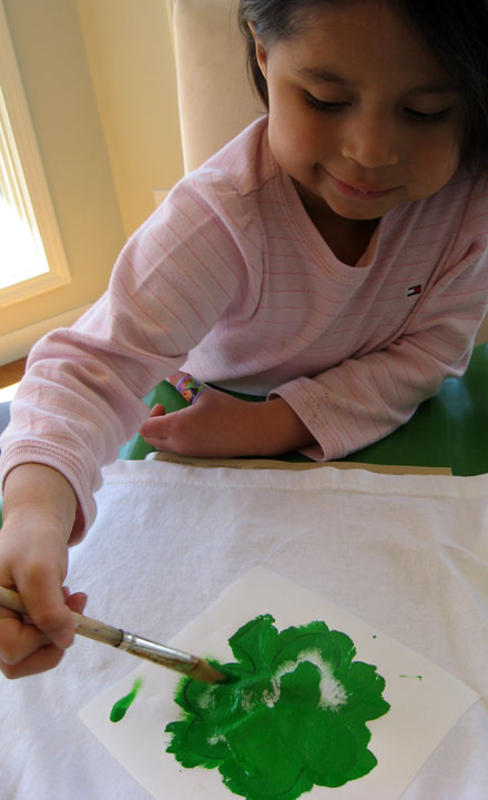 child painting shamrock with green paint