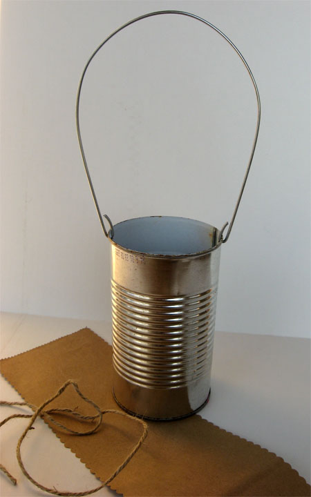 recycled tin can with two holes punched in it on opposite sides with a bent piece of coat hanger fed through the holes to make a handle making a a basket; there is a piece of scalloped cut brown paper an twine beside and under the can