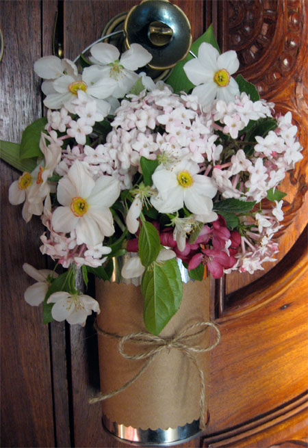 recycled may day basket with the brown paper and twine wrapped around filled with spring flowers and hung on a door knob