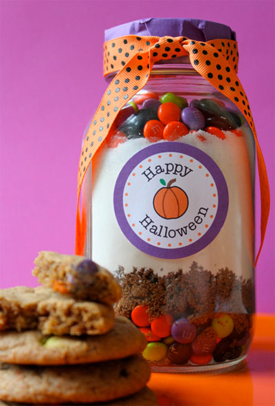 Printable Happy Halloween label on a quart jar filled with m&m cookie mix inside and a purple lid with orange and purple polka dot ribbon around the lid