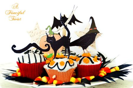 Cupcake printable toppers by Fanciful Twist. There's a ghost, pumpkin, black cat, black crow in a withches hat, and bat. Each topping a cupcake decorated in wite and black frosting and orange candy decorations