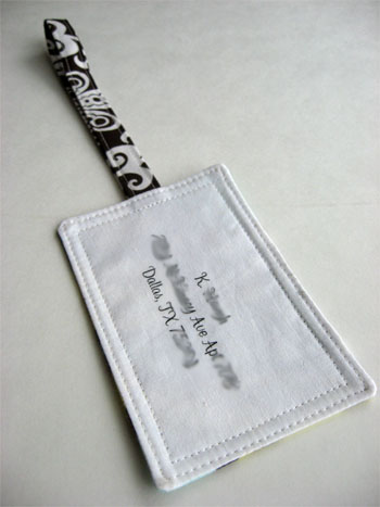 Luggage tag turned, pressed and edges stitched closing the opening.