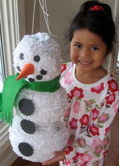 girl holding homemade snowman pinats