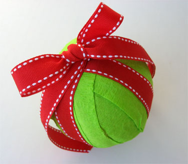green ornament wrapped with red ribbon