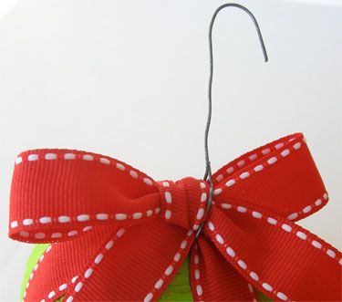 green ball ornament with red ribbon and ornament hook