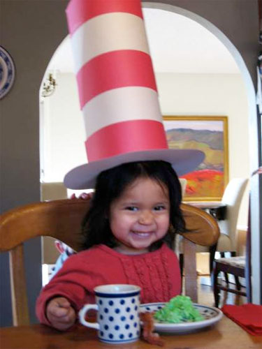 child wearing a crafted 'cat in the hat' hat eating green eggs and ham