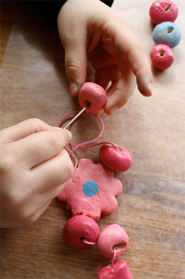 threading salt dough beads with needle