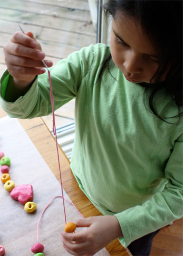child threading salt dough beads