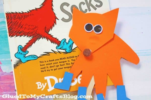 orange fox with blue socks puppet with the book fox in the socks book behind it to celebrate dr Suess