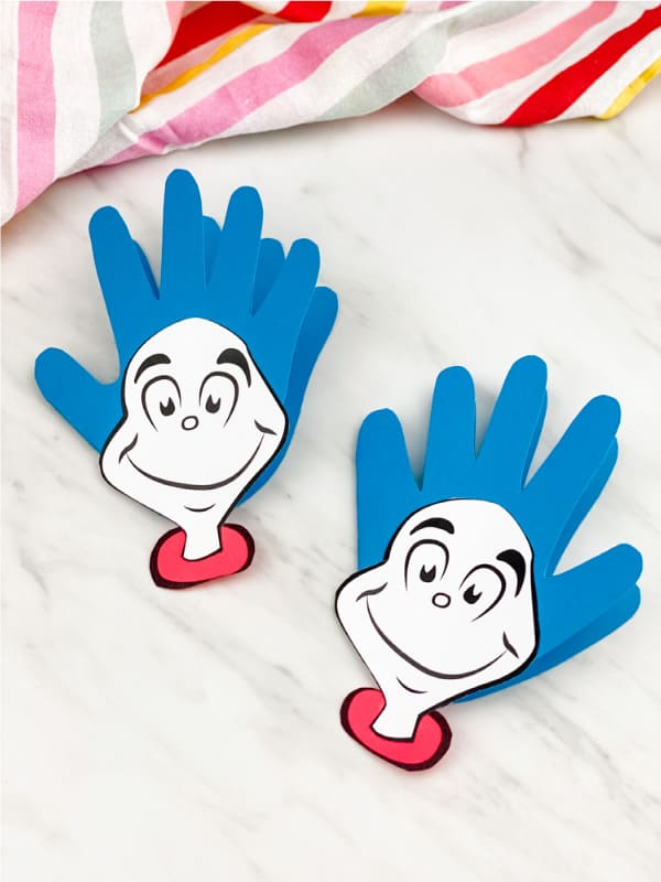 "celecbrate dr seuss with these handprint ""Thing 1 and Thing 2"" cards; the card is made of hand cut out of blue construction paper with printable faces glued to the palm region of the hand"