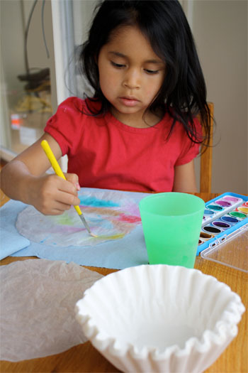 a child painting coffee filter for butterfly craft