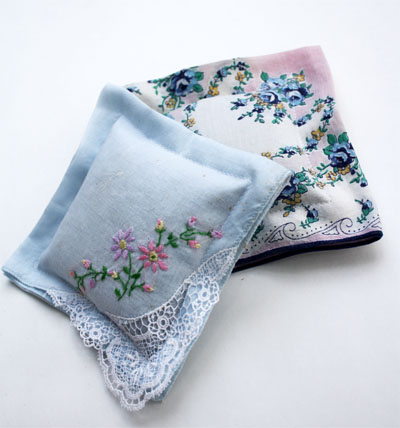 two completed handkerchief sachets, one is white with fower embroidery and lace on a corner, the other has a floral printed pattern on it