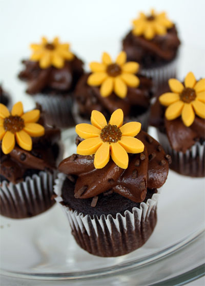 plate of chocolate frosted mini cupcakes with fondant sunflower on top