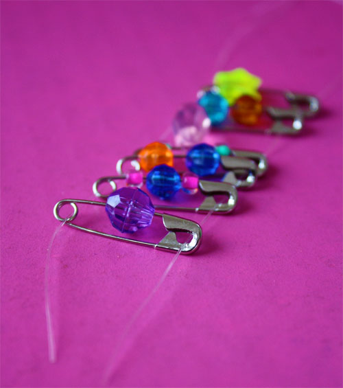 safety pins with beads laying on a table
