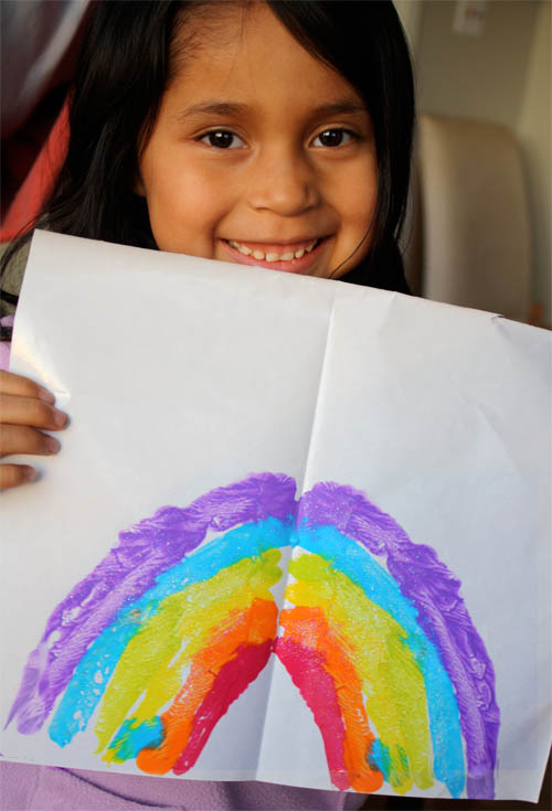 child holding rainbow painting