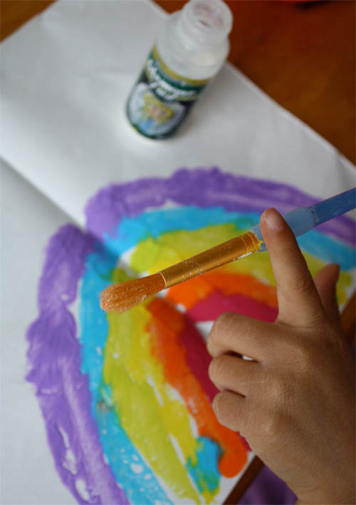 glitter dust on paintbrush, rainbow painting on table