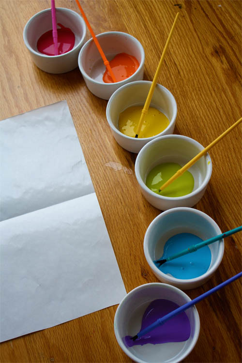 small bowls filled with paint and paintbrushes