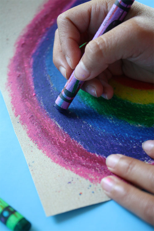 child's hand coloring a rainbow on sandpaper