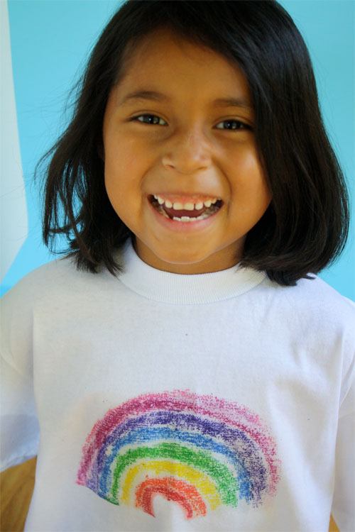 child wearing white shirt with rainbow printed with sandpaper on front