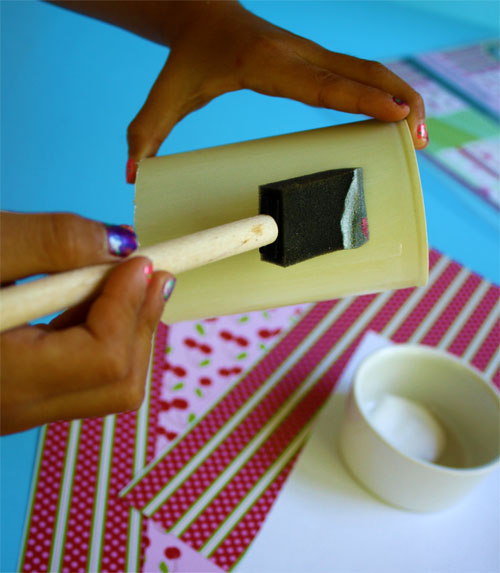 painting mod podge onto a paper container
