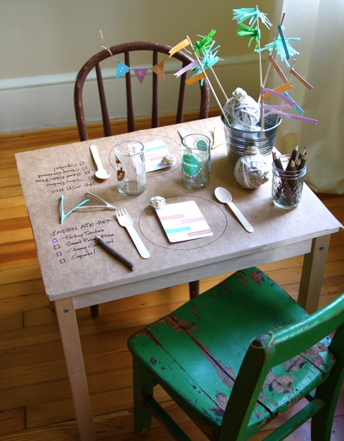 childs table covered with kraft paper, hand drawn place setting , checkist to try new foods