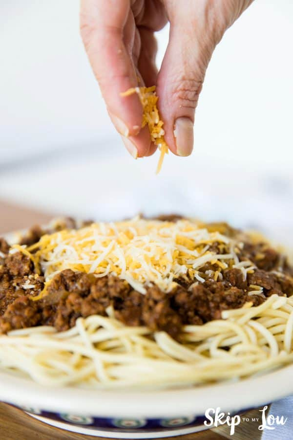 Cincinnati chili served on spaghetti with shredded cheese being sprinkled on to it; served in a white with blue trim detail bowl