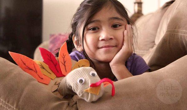child wearing turkey sock puppet