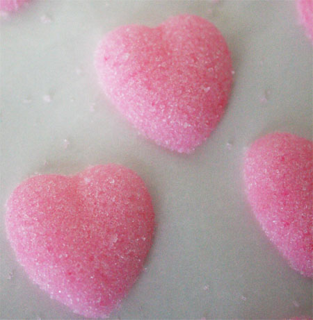 two pink heart sugar cubes on white background