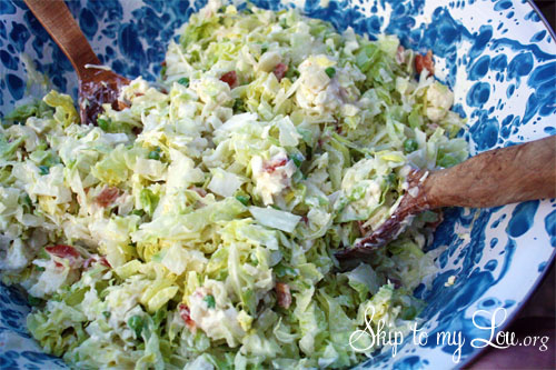 Tossed cauliflower salad with wooden salad forks in a blue and white bowl.