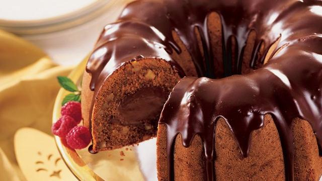 tunnel o' fudge pumpkin cake drizzed with chocolate glaze on a gold plate with raspberries garnishing the plate