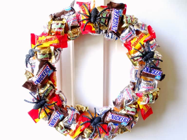 DIY Halloween decoration candy wreath with miniature candy bars and plastic black spiders on it