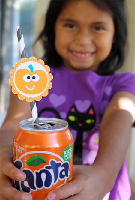Little girl holding a Fanta soda can that has a straw with free printable circle pumpkin Halloween tag attached.