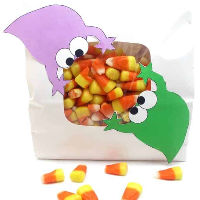 Candy corn party bag with clear window with a printable purple monster attached to the upper left corner and a green monster attached to the lower right corner of the window. It appears the monsters are eating the candy.