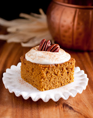 pumpkin bar with fuffy cream cheese frosting decorated with two pecans on top on a sccalop white dessert plate
