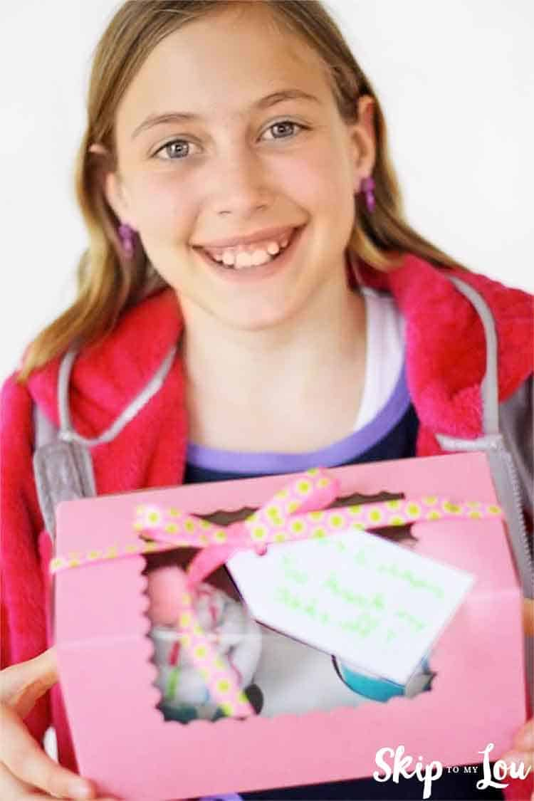 child holding sock cupcakes in bakery box