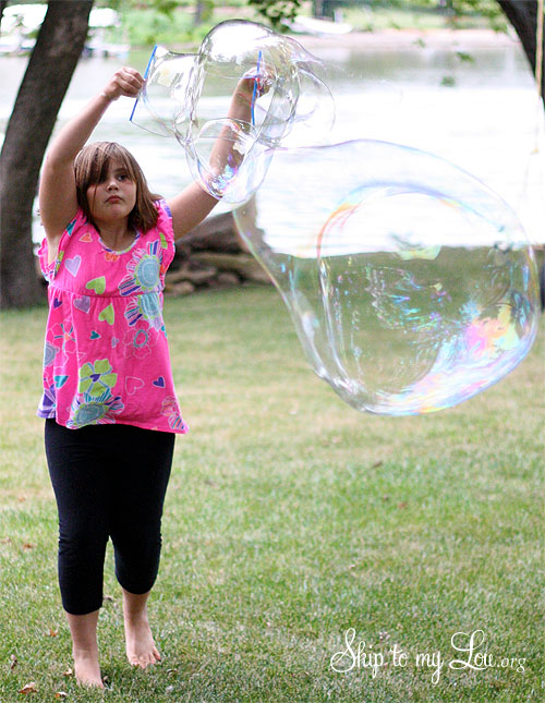 little girl plaing outside making a giant bubble with a diy giant bubble wand