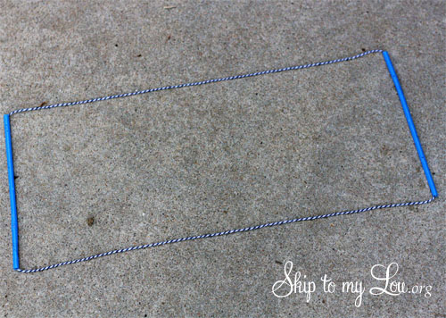 two yards of string fed through two straws with the ends tied together to make the giant bubble wand; the wand is laying on a flat surface in the shape of a rectangle with straws on opposite sides