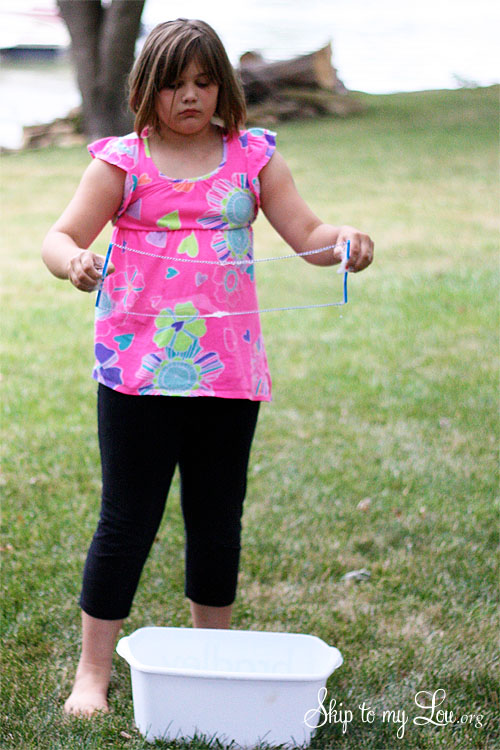 a little girl holding the wand filled with bubble solution ready to make a big bubble