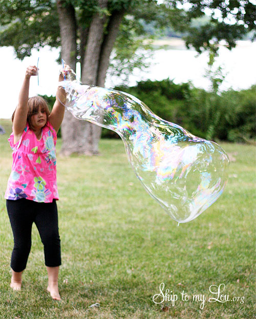 a little girl moving backwards holding the wand above her head allowing the motion and wind going through the wand to make a giant bubble