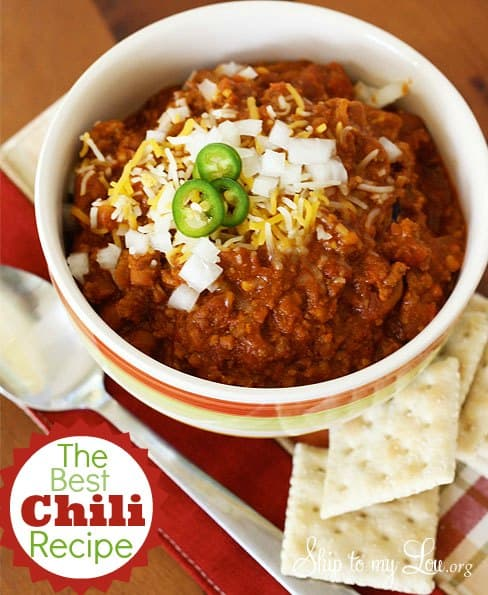A bowl of the best chili topped with shredded cheese, chopped onions, and slice jalapeños; there is a silver spoon and saltine crackers to the sides of the bowl
