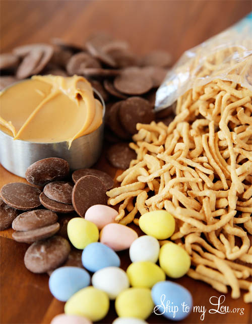 ingredients - chocolate melts, a cup of peanut butter, chow mein noodles and pastel colored candy coated chocolate mini eggs