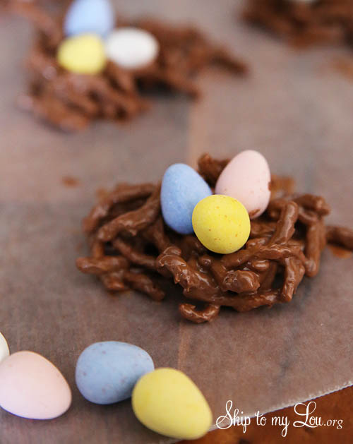 chocolate peanut butter nest cookies dropped onto waxed paper with three chocolate covered eggs placed in the center of the nest