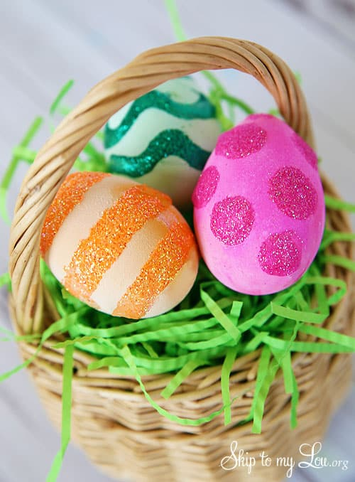 decorating Easter eggs - three glitter decorated eggs in a straw basket with fake green grass; there is a pink polka-dot egg, orange striped egg, and green wiggly stripped egg