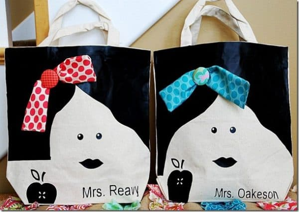 personalized teacher appreciation both totes have black hair, facial features, and apple fabric heat transfers applied, one has a red hair ribbon with name Mrs. Reavy, the second has a blue hair ribbon and the name Mrs. Oakeson on it
