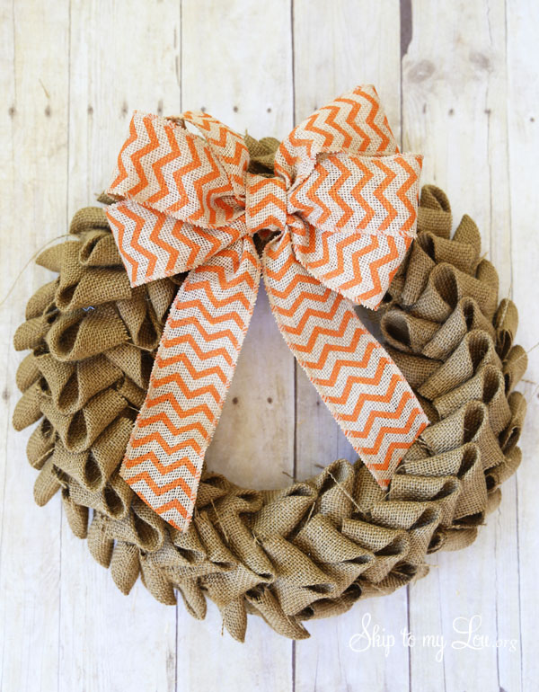 Burlap wreath with orange chevron bow on wood background